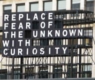 outdoor sign 'replace fear of the unknown with curiosity'