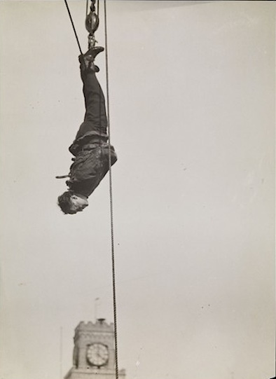 Houdini in straightjacket suspended from Times Square clock tower