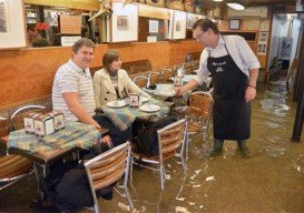 A waiter serves coffee to tourists in his flooded bar in Venice