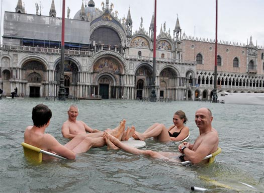 People sit at a table in a flooded Piazza San Marco in Venice