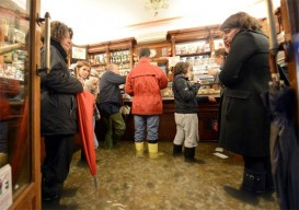 People have coffee in a flooded shop in Venice