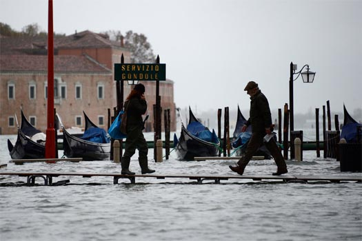 People walk on raised pathways set up near the flooded Piazza San Marco in Venice