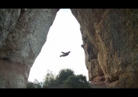 obsessive wingsuit flight through a hole in a mountain