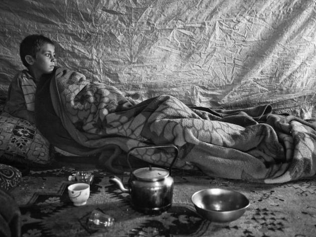 Faysal, 6, waking up inside his family's tent a settlement in the Bekaa Valley, Lebanon. (Moises Saman/Magnum Photos for Save the Children)