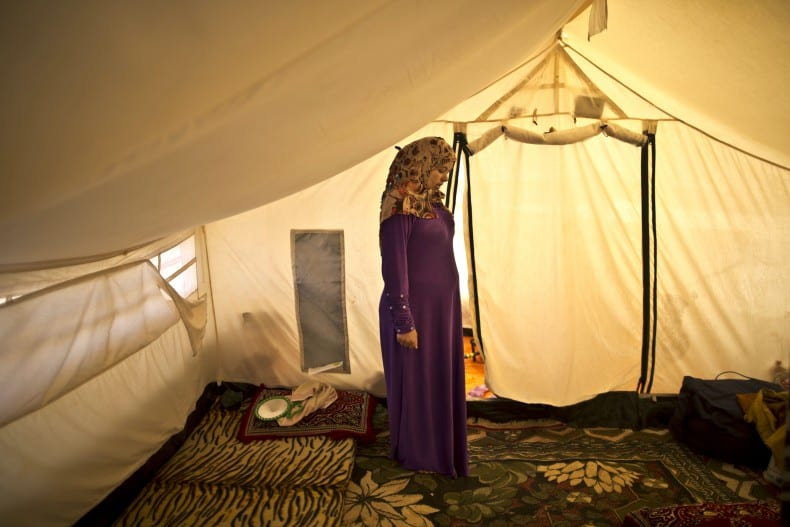 In this Tuesday, March 17, 2015 photo, Syrian refugee Adala Ismail, 32, who is six months pregnant, poses for a portrait inside her tent at an informal settlement near the Syrian border, on the outskirts of Mafraq, Jordan. Expectant mothers in these settlements often can't afford doctor visits and face potential health hazards because of lack of running water and other challenges. By contrast, pregnant women in Jordan's three recognized refugee camps have access to free services, including pre-natal care and delivery, according to the U.N. refugee agency. (AP Photo/Muhammed Muheisen)